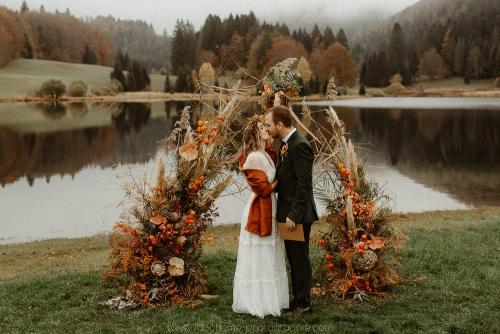 arche de mariage laïque devant le lac, décoration automnale, premier baiser